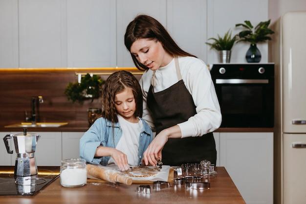 Mãe e filha cozinhando juntas na cozinha
