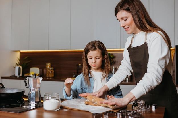 Mãe e filha cozinhando na cozinha de casa