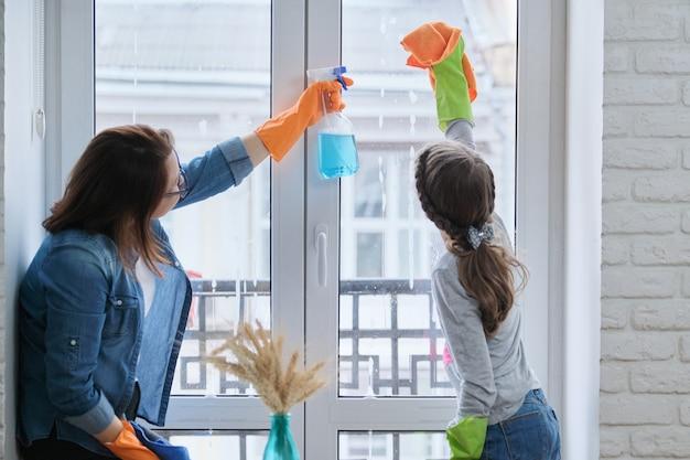 Mãe e filha criança em luvas de borracha com detergente e pano, lavando janelas juntas