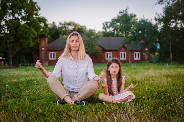 Mãe e filha criança meditar juntos em posição de lótus ao ar livre.