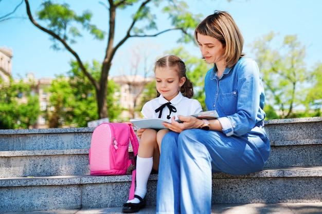 Mãe e filha criança sentada na escada e ler livro, estudar lições.
