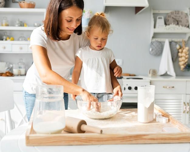 Mãe e filha curiosa cozinhando juntos