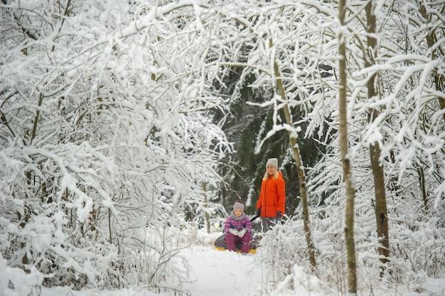 Mãe e filha da família no inverno com um círculo inflável caminham pela floresta coberta de neve