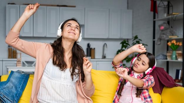 Mãe e filha dançando e ouvindo música