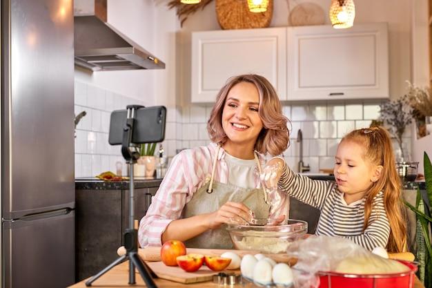 Mãe e filha de blogueira de comida preparando a massa, assar biscoitos, gravar vídeo na câmera, desfrutar. na cozinha