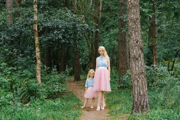 Mãe e filha de cinco anos com as mesmas roupas românticas andando no parque ou na floresta