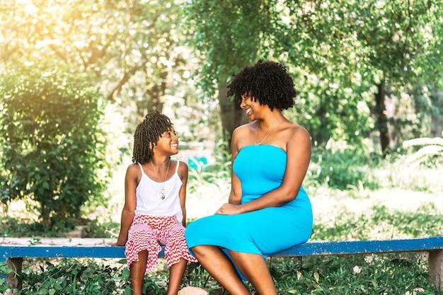 Mãe e filha de etnia afro-americana, sentadas em um parque, olhando uma para a outra e conversando