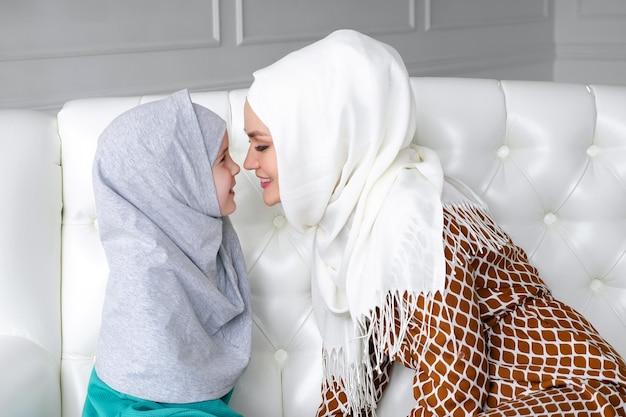 Mãe e filha de família muçulmana em hijabs e roupas tradicionais estão sentadas no sofá em casa, esfregando suavemente o nariz e a mãe está beijando as mãos de sua filha.
