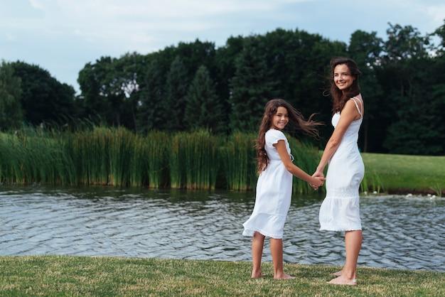 Mãe e filha de lado posando no lago