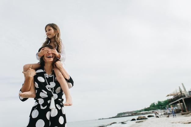 Mãe e filha de mãos dadas e andando na praia.
