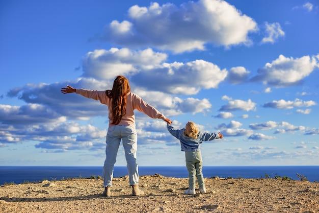 Mãe e filha de mãos dadas e olhando para cima admirando as incríveis nuvens sobre o mar viajam c