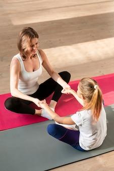 Mãe e filha de mãos dadas em tapetes de ioga