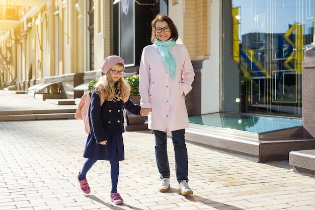Mãe e filha de mãos dadas, levando juntos para a escola
