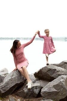 Mãe e filha de mãos dadas no fundo do rio