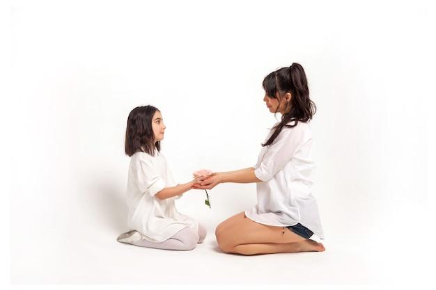 Mãe e filha de meia-idade com roupas brancas segurando uma flor nas mãos