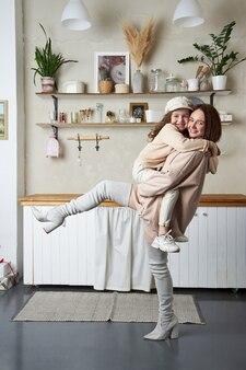 Mãe e filha de moda beleza. sessão de fotos de família, alegria e emoções divertidas. mulher e uma garota se abraçam
