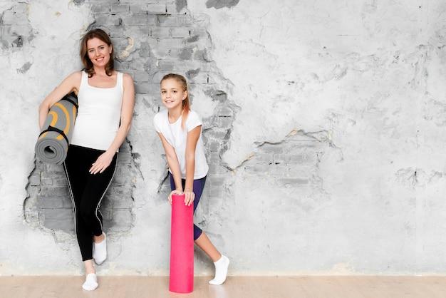 Mãe e filha de tiro completo segurando tapetes de ioga com cópia-espaço