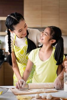 Mãe e filha de tiro médio na cozinha