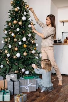 Mãe e filha decoram a árvore de natal dentro de casa