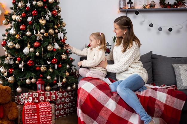 Mãe e filha decoram a árvore de natal em casa