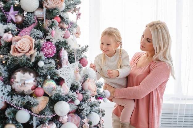 Mãe e filha decoram a árvore de natal rosa dentro de casa.