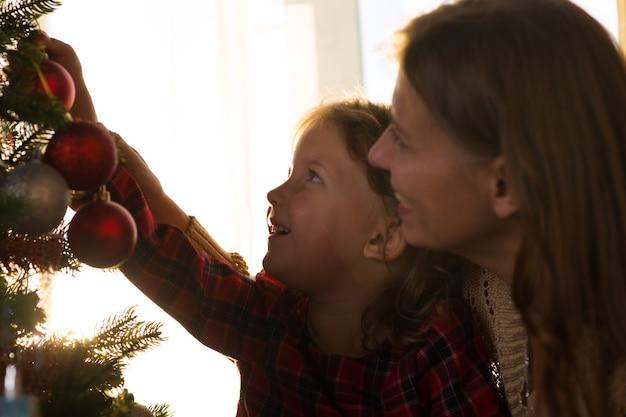 Mãe e filha decoram uma árvore de natal contra a janela com um sol poente e um sol forte