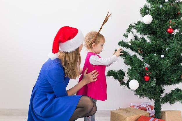 Mãe e filha decorando a árvore de natal e se divertindo. feriados e conceito de celebração.