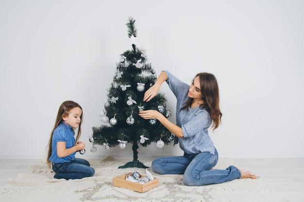 Mãe e filha decorando a árvore de natal
