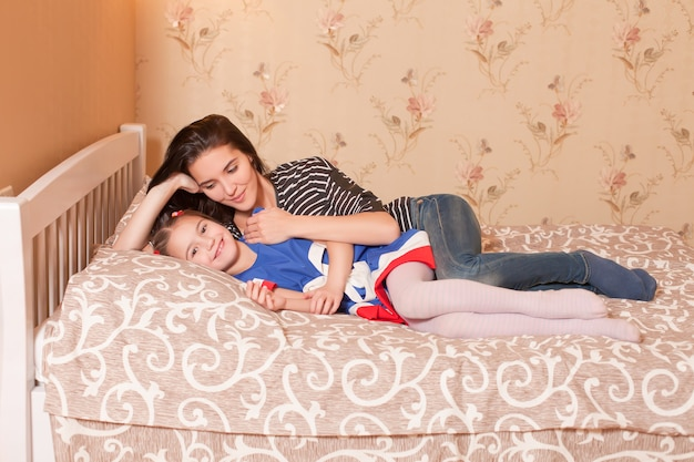 Mãe e filha deitada na cama.
