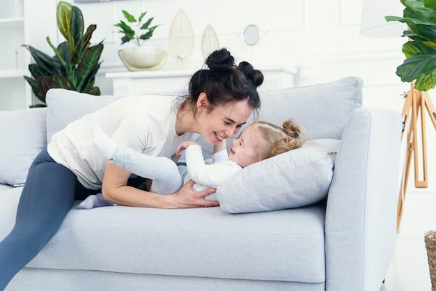 Mãe e filha, deitada no sofá na sala de estar.