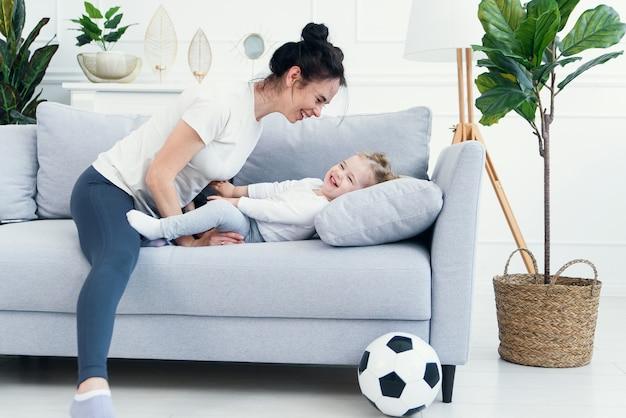 Mãe e filha deitada no sofá na sala de estar.
