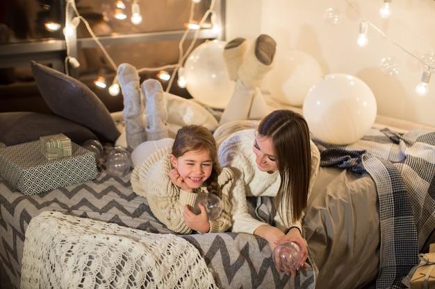 Mãe e filha deitadas na cama na véspera de natal, no aconchegante interior da casa