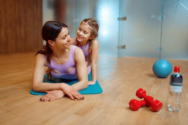 Mãe e filha deitados juntos na esteira no ginásio, treino de fitness, ginástica.