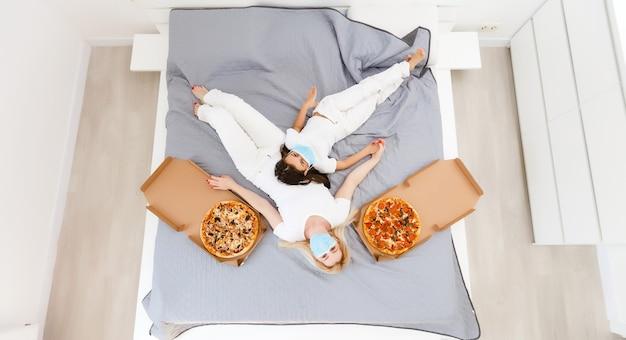 Mãe e filha deitam-se na cama em casa com pizza durante a quarentena, quarentena de lazer