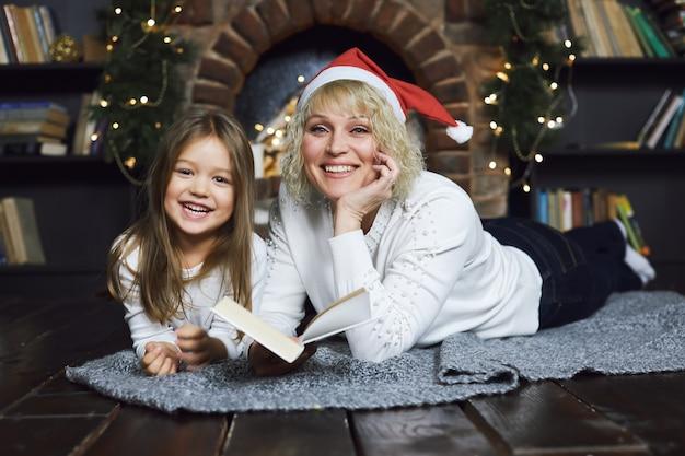 Mãe e filha deitar no chão e ler um livro contra a lareira