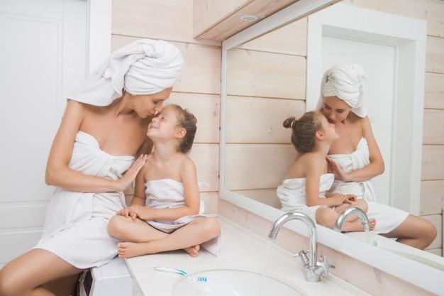 Mãe e filha dela abraçando no banheiro.