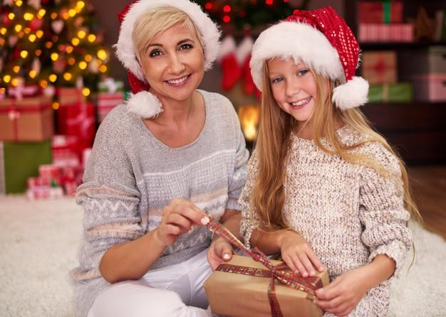 Mãe e filha desembrulhando alguns presentes de natal