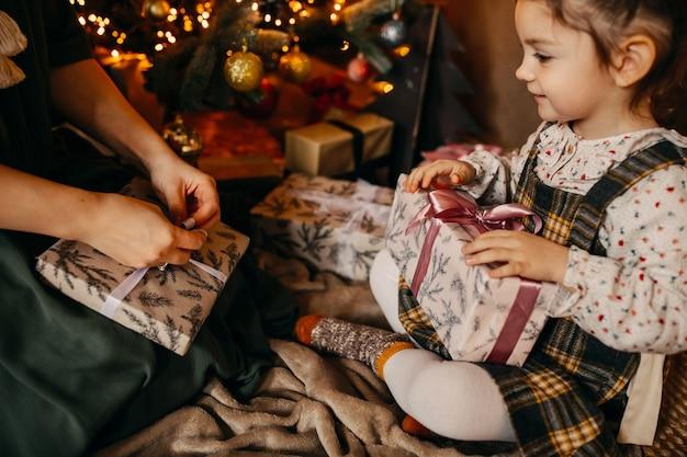 Mãe e filha desembrulhando presentes, sentadas ao lado de uma árvore de natal