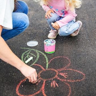 Mãe e filha desenham flores com giz de cera colorido no asfalto dia de verão