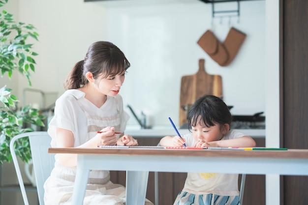 Mãe e filha desenhando em casa