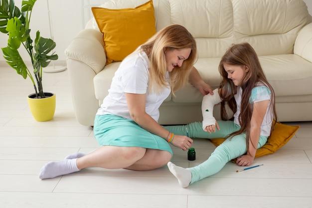 Mãe e filha desenhando uma imagem em bandagem usando tintas conceito de terapia de jogo