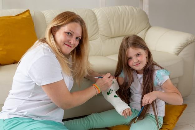 Mãe e filha desenhando uma imagem na bandagem usando o conceito de terapia de jogo de tintas