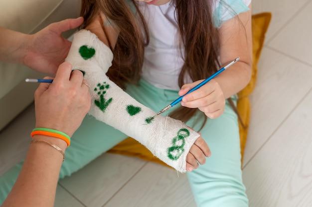 Mãe e filha desenho imagem na bandagem usando close-up de tintas. conceito de terapia de jogo.