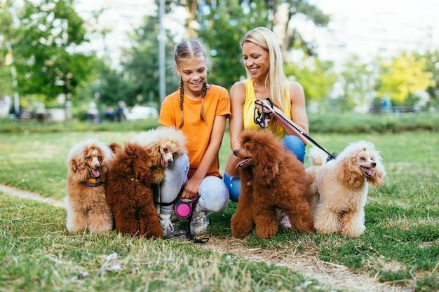 Mãe e filha desfrutando junto com seus poodles no parque.