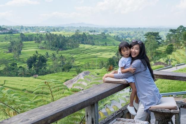 Mãe e filha desfrutar de vista do campo de arroz em casca