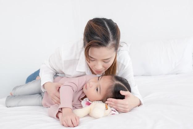 Mãe e filha desfrutar na cama em casa