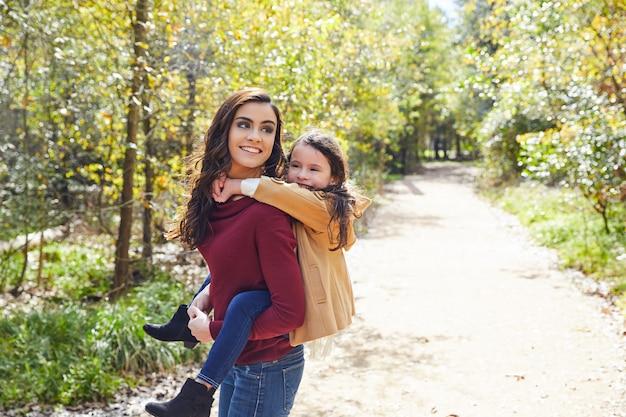 Mãe e filha divertida piggyback em um parque