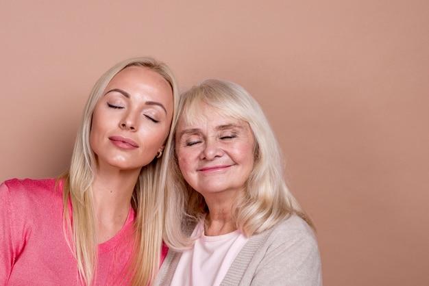 Mãe e filha do close-up com os olhos fechados