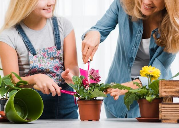 Mãe e filha do close-up que plantam flores