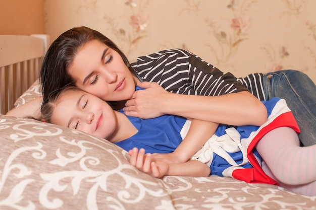 Mãe e filha dormem na cama.